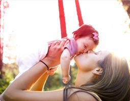 Kuva naisesta suukottamassa ja nostamassa vauvaa.
