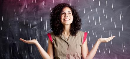Kuva nuoresta naisesta seisomassa liitutaulun edessä.