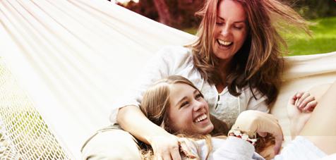 Kuva kahdesta naisesta hymyilemässä riippukeinussa.