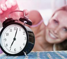 Kuva herätyskellosta, ja taka-alalla olevasta naisesta, joka ojentuu sulkemaan herätyksen pois.