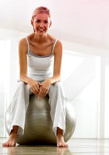 Kuva naisesta treenivaatteissa istumassa treenipallon päällä. Kuva kuvastaa liikunnan tärkeyttä kuukautistenkin aikana.