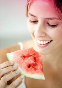 Kuva naisesta syömässä vesimelonia. Kuva kuvastaa vinkkejä kuukautiskipujen hoitoon - Syö hedelmiä ja kasviksia, jotka sisältävät paljon vettä.