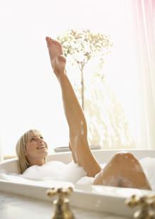 Kuva naisesta kylpyammeessa venyttämässä jalkaansa ylöspäin. Kuva kuvastaa rentoutumista kuukautisten aikana.