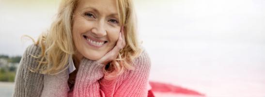 Keski-ikäinen nainen hymyilemässä kuvan vasemmassa laidassa.