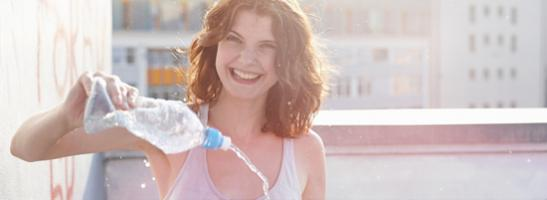 Kuva nuoresta naisesta puristamassa vesipulloa, josta suihkuaa vettä.