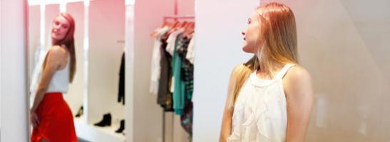 Kuva tytöstä seisomassa peilin edessä, kokeilemassa vaatteita.