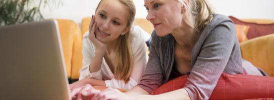 Kuva äidistä ja tyttärestä käyttämässä tietokonetta yhdessä. Kuva kuvastaa kommunikoinnin tärkeyttä ja tyttären auttamista oikean tiedon löytämisessä.