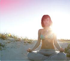 Bilde av en kvinne som sitter på stranden og mediterer. Bildet viser, att det går an å slappe av og leve som vanlig, også når du har menstruasjon.